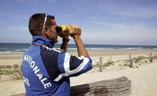 Un maître-nageur sauveteur de la police nationale observe la côte aquitaine à la jumelle le 2 août 2007 sur la plage du Porge près de Lacanau.