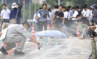 Mesure de la température au sol sur un trottoir arrosé à Tokyo, le 13 août 2018.
