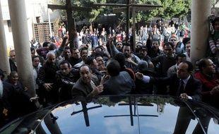Des chrétiens d'Egypte manifestent autour de la voiture du grand Imam d'Al-Azhar, Ahmed al-Tayeb, venus présenter ses condoléances au patriarche copte orthodoxe Chenouda III, au Caire, le 2 janvier 2011.