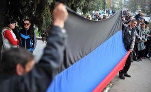 """Des pro-russes brandissent un drapeau de l'autoproclamée """"République de Donetsk"""" lors d'un rassemblement séparatiste, le 18 avril 2014 à Slaviansk, en Ukraine"""