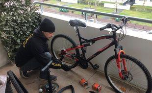 Arthur, réparateur de vélos chez Cyclofix, intervient au domicile de Brigitte, 57 ans, pour changer la chambre à air du vélo de son fils.