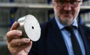 Le chef du Management de la société McPhy Energy, Pascal Mauberger, tient dans la main une galette métallique, le 6 novembre 2015 à La Motte-Fanjas dans le sud-est