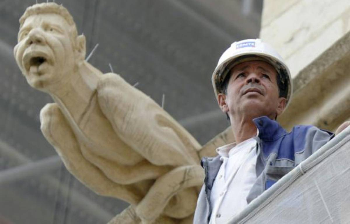 Le chef de chantier, Mohamed Benzizine, à côté d'une gargouille de la cathédrale Saint-Jean à son effigie, le 6 septembre 2016 à Lyon – PHILIPPE DESMAZES AFP