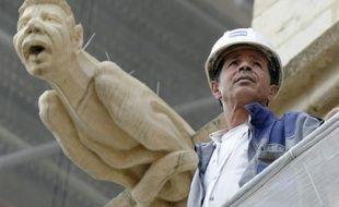 Le chef de chantier, Mohamed Benzizine, à côté d'une gargouille de la cathédrale Saint-Jean à son effigie, le 6 septembre 2016 à Lyon