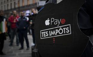 Un membre d'Attac manifeste contre l'évasion fiscale devant un magasin Apple en novembre 2017.