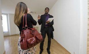 Illustration: Une jeune femme visite un appartement avec un agent immobilier.