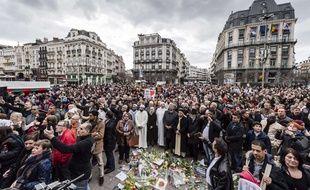 Foule rassemblée pour une minute de silence en hommage aux victimes des attentats, place de la Bourse à Bruxelles, le 22 mars 2017.