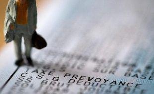 Une figurine sur un bulletin de salaire mentionnant la CSG