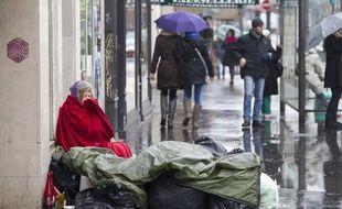 Paris le 27 janvier 2013. SDF Sans Domicile Fixe sans abris entoure de poubelle. Femme a la rue.