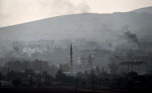 De la fumée au-dessus de la ville de Kobané, où les forces kurdes combattent les jihadistes de l'EI, le 17 octobre 2014 à Mursitpinar, à la frontière syro-turque
