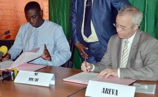 Luc Oursel, le président du directoire d'Areva (d) et Omar Hamidou Tchiana, le ministre nigérien des Mines, signent un accord sur les mines d'uranium le 26 mai 2014 à Niamey