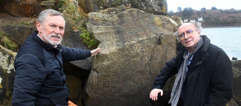 Les deux vainqueurs du concours posent devant la fameuse inscription gravée sur le rocher.