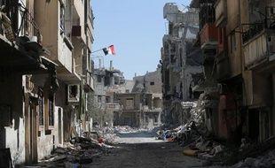 Le drapeau syrien flotte au balcon dans une rue dévastée de Homs, en Syrie, le 31 juillet 2013.