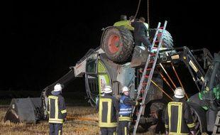 Des pompiers près de la pelleteuse qui a basculé en Allemagne, tuant un jeune homme et blessant cinq autres personnes lors d'un défi lancé sur Facebook, le 29 juillet 2014.
