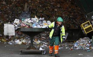 Un employé de la société GDE transporte des déchets recyclables.