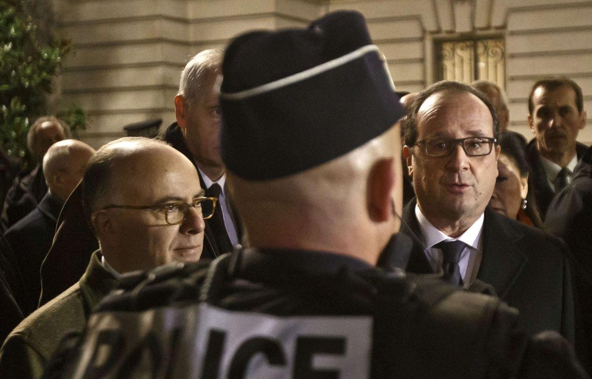 Le ministre de l'Intérieur Bernard Cazeneuve et le président François Hollande avec un officier de police, le 31 décembre 2015 à Paris. – Michel Euler/AP/SIPA