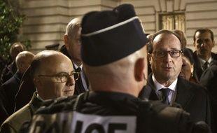 Le ministre de l'Intérieur Bernard Cazeneuve et le président François Hollande avec un officier de police, le 31 décembre 2015 à Paris.