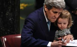 Le secrétaire d'Etat américain  John Kerry signe l'accord sur le climat, tenant sa petite-fille, le 22 avril 2016 à l'ONU à New York