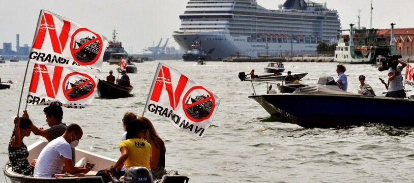 Des militants environnementaux brandissent des banderoles «Non aux navires de croisière» à bord de petites embarcations à moteur dans la lagune de Venise, alors que le MSC Orchestra quitte Venise, le 5 juin 2021.