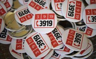 Des badges aux couleurs du 39 19, le numéro d'appel d'urgence en cas de violences conjugales.