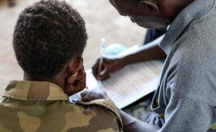 Un ancien enfant-soldat est pris en charge par un membre de l'UNICEF le 27 mai 2013 à Bangui