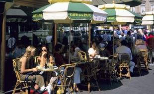 Des touristes en terrasse du Café de la Paix à Paris