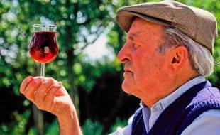 Illustration: Un vigneron regarde la couleur de son vin.