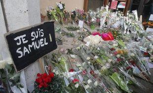 Des fleurs déposées devant le collège où enseignait le professeur d'histoire-géographie assassiné vendredi à Conflans-Sainte-Honorine.