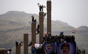 Des partisans du président yéménite Ali Abdullah Saleh se tiennent sur des colonnes pendant une manifestation à Sanaa, Yémen, le 1er avril 2011.