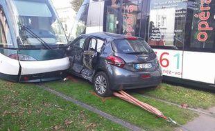 La voiture est restée coincée entre deux trams.