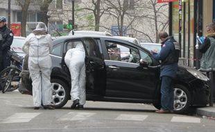 Rue de Meaux (19e), la voiture laissÈe au travers de la route par les auteurs de la fusillade de Charlie Hebdo est scrutÈe de prËs par des enquÍteurs de la police scientifique et judiciaire.