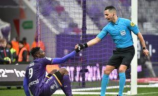 L'arbitre Karim Abed aide l'attaquant du TFC Yaya Sanogo à se relever, dimanche contre Reims.