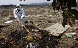 Un policier recherche des disparus après le séisme qui a frappé le Japon le 11 mars 2011, près de Fukushima.
