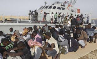 Des migrants devant un navire des gardes-côte à Khoms, en Libye, le 1er octobre 2019.