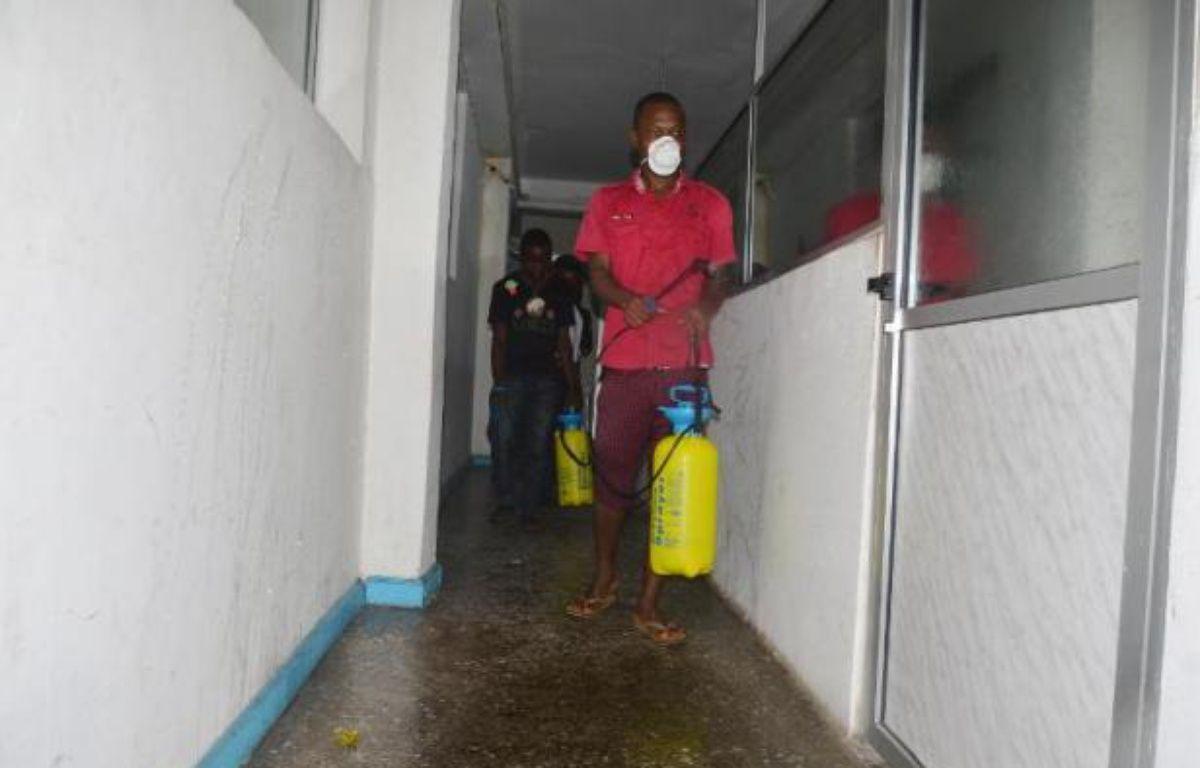 Un employé désinfecte un bureau à Monrovia au Libéria contre la fièvre Ebola le 1er août 2014 – Zoom Dosso AFP