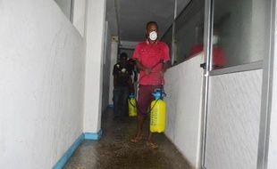 Un employé désinfecte un bureau à Monrovia au Libéria contre la fièvre Ebola le 1er août 2014