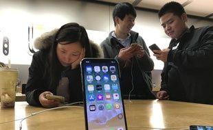 De jeunes chinois testent l'iPhone X dans un Apple store de Beijing en Chine, le 6 novembre 2017.