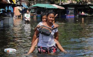 Quelques centaines de personnes dont les habitations dans le Nord-Est de Bangkok sont inondées depuis des jours, ont réclamé lundi une évacuation plus rapide de l'eau, accusant les autorités de les sacrifier pour protéger le centre de la capitale toujours au sec.
