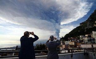 Des badauds prennent des photos de l'Etna en éruption, le 4 décembre 2015 à Taormina en Sicile