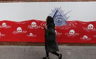 Une femme passe à côté d'une fresque anti-américaine sur l'ancien bâtiment de l'ambassade américaine à Téhéran (Iran)