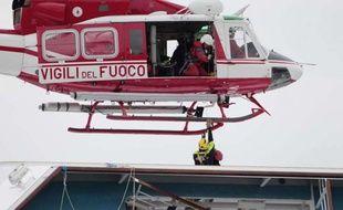 Un hélicoptère survole l'épave du navire de croisière Costa Concordia, le 16 janvier 2012, au large de la Toscane.