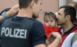 Un réfugié tient son enfant dans ses bras et attend un train spécial à la gare de Freilassing, près de la frontière autrichienne, le 15 septembre 2015