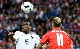Le milieu de terrain français Paul Pogba face au Suisse Valon Behrami lors de l'Euro, le 19 juin 2016 à Lille