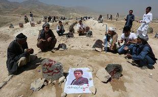 Des villageois en pleine prière devant les tombes des victimes du double attentat perpétré samedi 23 juillet 2016 à Kaboul.