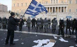 Un manifestant agite un drapeau grec devant le Parlement, sur la place Syntagma à Athènes (le 12 février 2012)