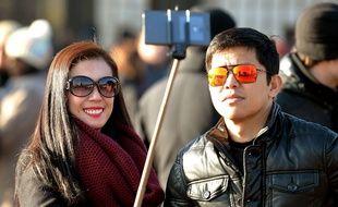 Des touristes utilisent une perche à selfie à Londres.