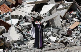 Une femme près des décombres d'un bâtiment abritait l'Associated Press, le radiodiffuseur Al-Jazeera et d'autres médias, dans la ville de Gaza, le 16 mai 2021.