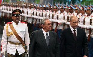 Le président russe Vladimir Poutine (d) reçu à Cuba par son homologue cubain Raul Castro (c) Place de la Révolution à La Havane le 11 juillet 2014