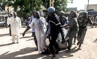 Des membres des forces de sécurité transportent une victime de l'attentat qui a frappé Maroua, au Cameroun, le 22 juillet 2015.