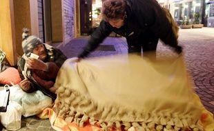 Une dame distribue une couverture à un sans - abri. Illustration
